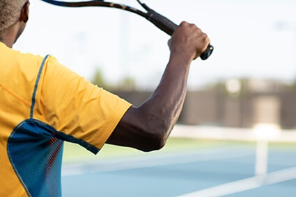 Man with elbow pain swinging tennis racket